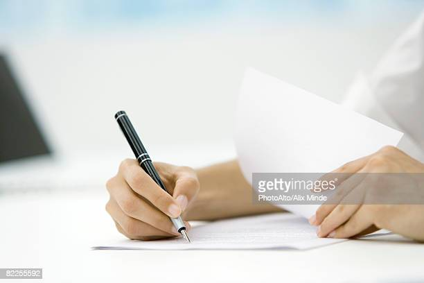 Person signing document with pen, cropped view of hands