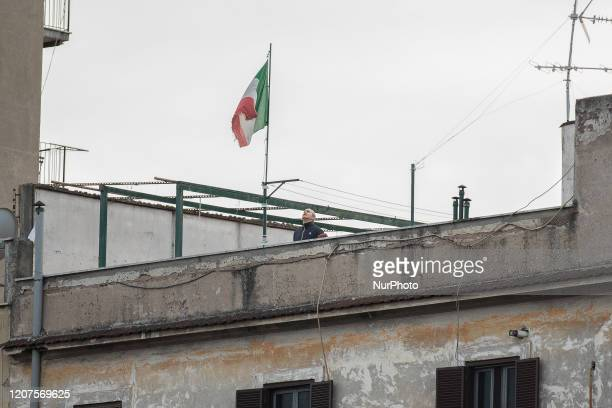 A person sings the Italian national anthem in front of the tricolor flag flying on the terrace of a building in the Pigneto district in Rome on March...