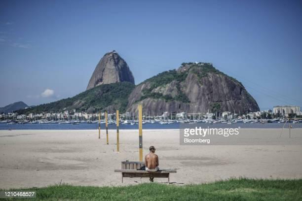 A person sits alone at a nearly empty Botafogo beach in Rio de Janeiro Brazil on Monday April 20 2020 President Jair Bolsonaro has urged Brazilians...
