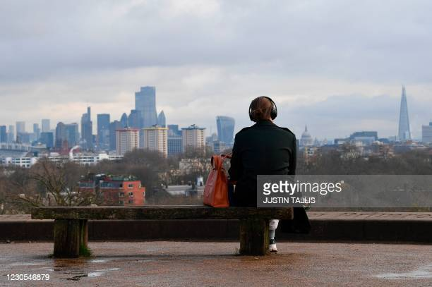 Person sits alone on a bench on the top of Primrose Hill in London on January 12, 2021 as life continues under Britain's third lockdown since the...