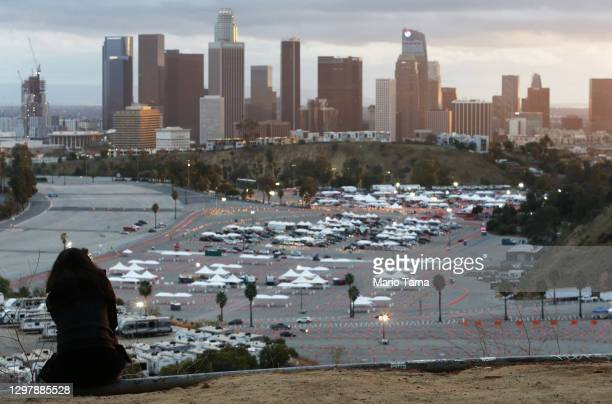 Person sits on a hillside as cars are lined up with people waiting to receive vaccines at a mass COVID-19 vaccination site at Dodger Stadium, with...