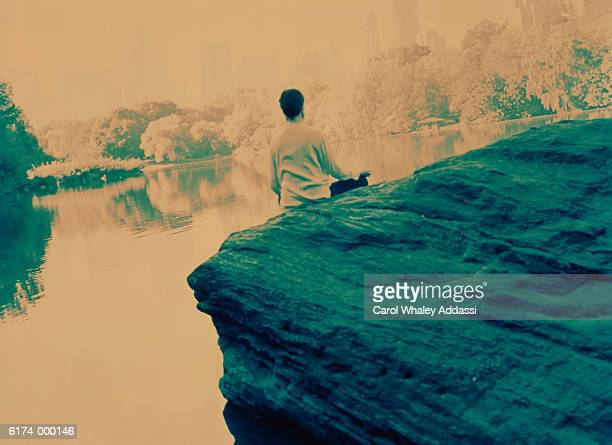 Person Sits on Rock by Lake