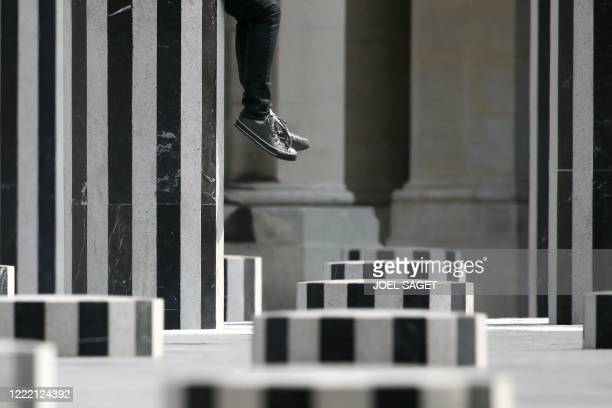 Person sits on the Daniel Buren columns set up in the inner yard of the Palais Royal in central Paris on April, 16 2010. AFP PHOTO JOEL SAGET