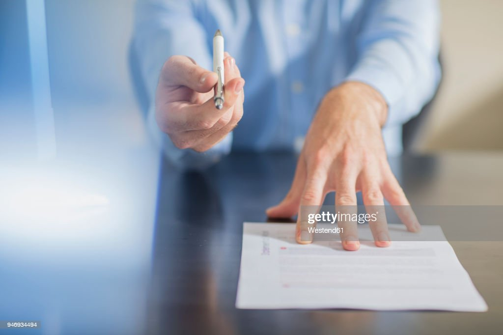 Person sitting at office desk presenting ballpen and contract : Stock Photo
