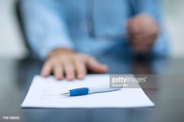Person sitting at office desk with documents and a pen