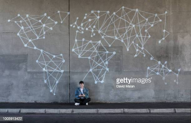 person sitting in front of a wall with a world map, network illustration. - one world stock pictures, royalty-free photos & images