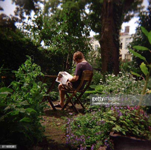 person sitting in garden reading a magazine - nature magazine stock pictures, royalty-free photos & images