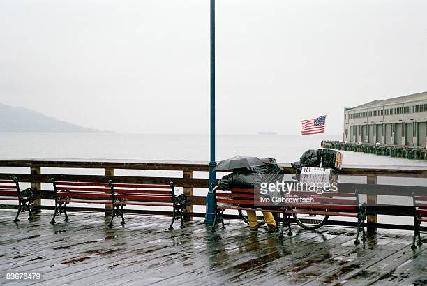a person sitting on a bench in the rain, overlooking san francisco bay, usa - san francisco homeless stock photos and pictures