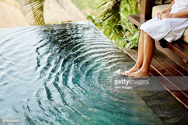 a person sitting on a bench with her feet in the shallow water of a pool, making ripples.  - frau gespreizte beine stock-fotos und bilder