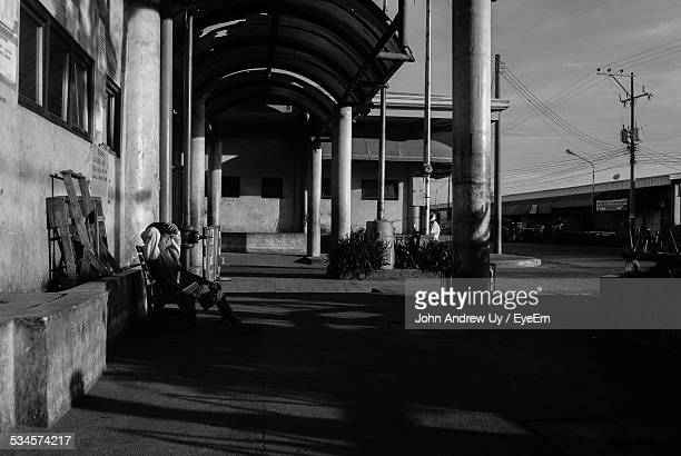 Person Sitting On Bench Outside Old Station