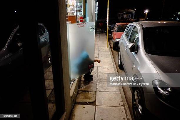 Person Sitting On Doorway Of Store By Car At Night