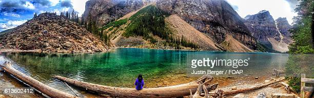 Person sitting on log exploring Moraine Lake