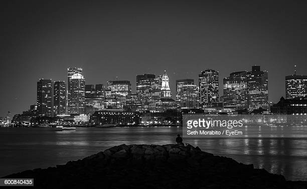 Person Sitting On Rocks By Sea And Illuminated City Skyline At Night
