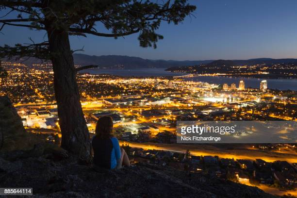 person sitting under a tree in knox mountain park looking down at downtown kelowna, british columbia, canada - kelowna stock pictures, royalty-free photos & images