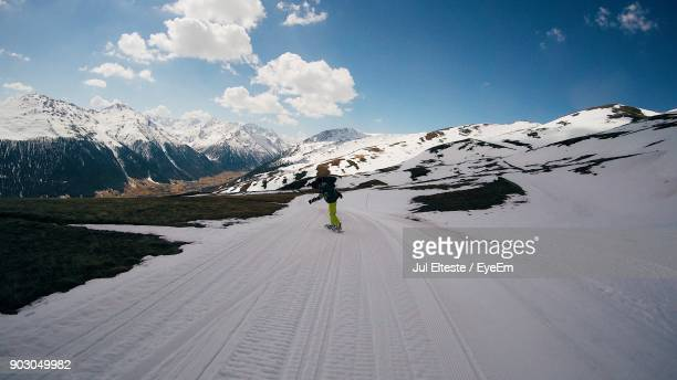 person skateboarding on snow covered road against sky - jul photos et images de collection