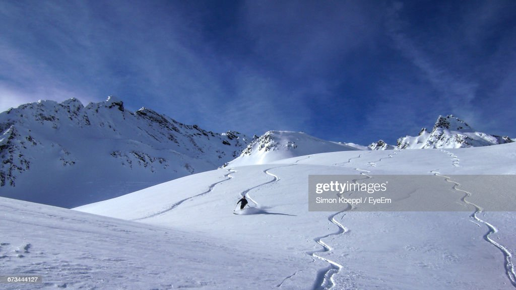 Person Skiing On Ski Slope By Snowcapped Mountains Against Sky : Stock Photo