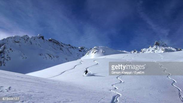 Person Skiing On Ski Slope By Snowcapped Mountains Against Sky