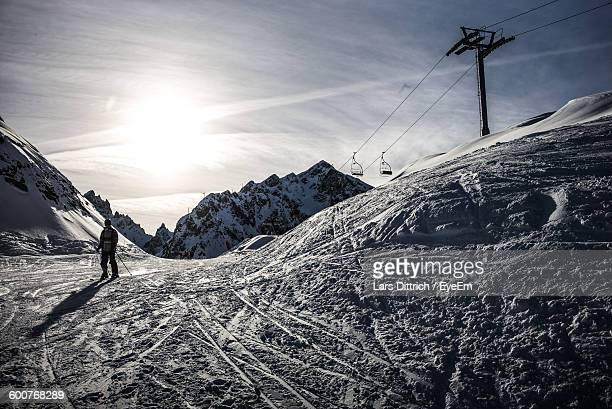 Person Skiing On Snow Covered Field By Mountains Against Sky