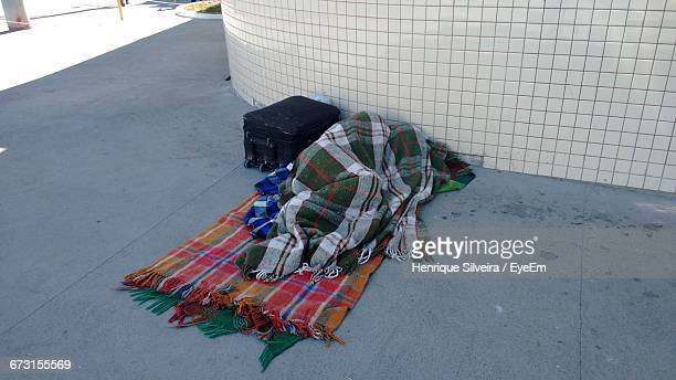 Person Sleeping On Street In Blanket By Luggage