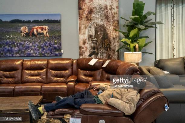 Person sleeps on a couch while taking shelter at Gallery Furniture store which opened its door and transformed into a warming station after winter...