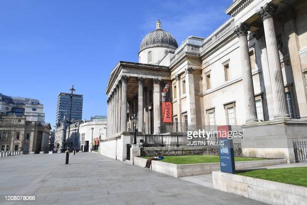 A person sleeps on the wall outside the National Gallery in Trafalgar Square in central London on March 24 2020 after Britain ordered a lockdown to...