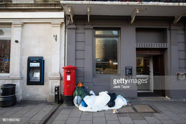 A person sleeps rough in front of a bank on January 5 2018 in Windsor England British Prime Minister Theresa May has publicly challenged comments...