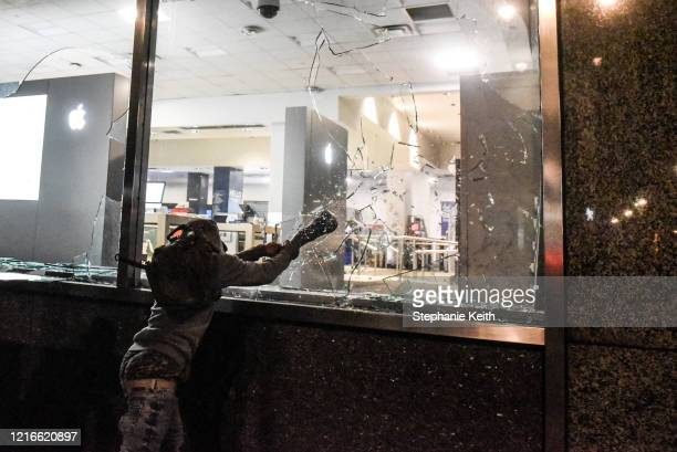 A person smashes a window of a Best Buy store on May 31 2020 in New York City Major cities across the United States have seen increased protests...