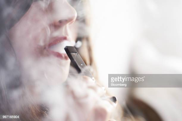 A person smokes a Juul Labs Inc ecigarette in this arranged photograph taken in the Brooklyn Borough of New York US on Sunday July 8 2018 Juul Labs...