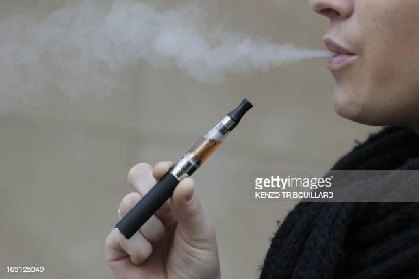 A person smokes an electronic cigarette on March 05 2013 in Paris AFP PHOTO / KENZO TRIBOUILLARD