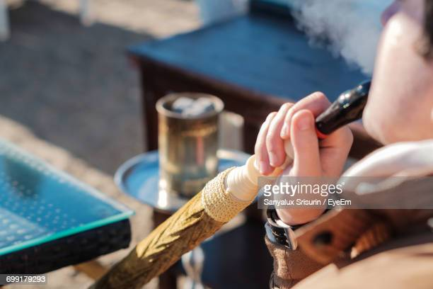 person smoking water pipe while sitting outdoors - hookah stock photos and pictures
