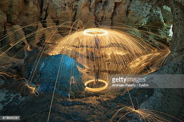Person Spinning Wire Wool Amidst Rock