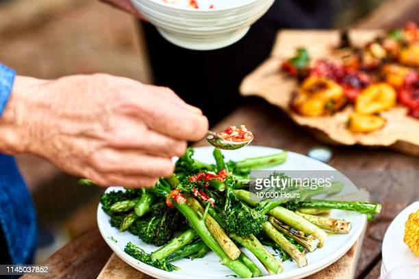 person spooning sauce over freshly cooked green vegetable medley - vegetarian food stock pictures, royalty-free photos & images