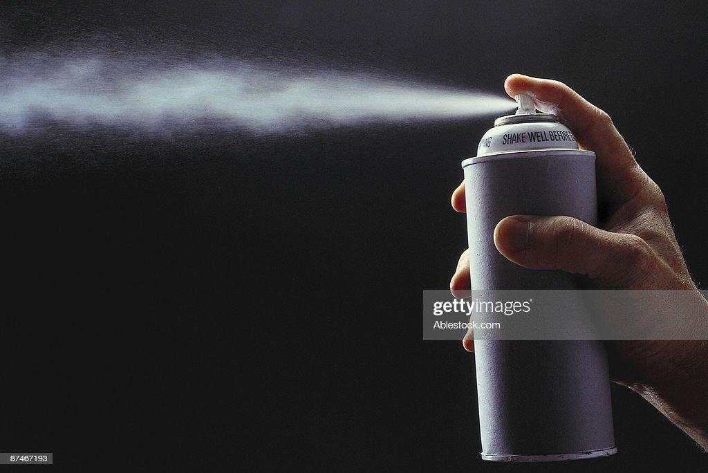 Person spraying aerosol can : Stock Photo