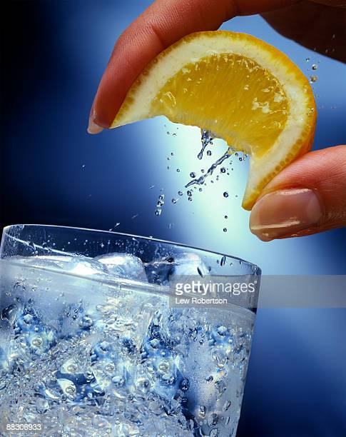 person squeezing lemon into water - carbonated water stock pictures, royalty-free photos & images