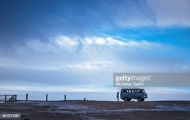 Person Standing Bear Van On Field Against Sky During Winter