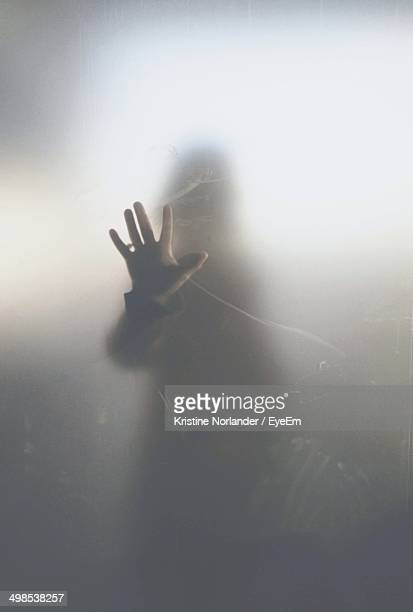 person standing behind glass window - human trafficking stock photos and pictures