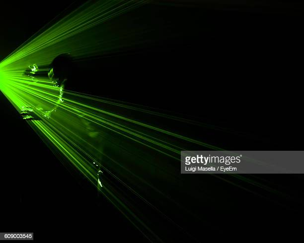 Person Standing By Laser Beams At Nightclub