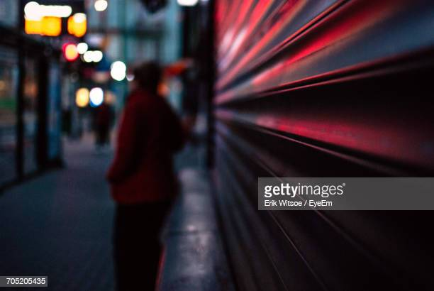 person standing by shutter of store at night - shutter stock pictures, royalty-free photos & images