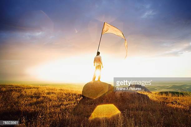 Person standing in field with flag
