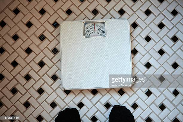 Person standing in front of bathroom scales