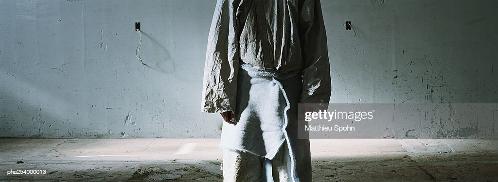 Person standing in front of wall, mid-section : Stockfoto