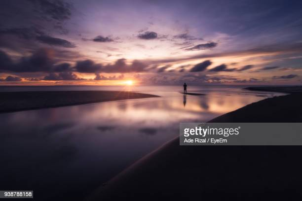 person standing in sea against sky during sunset - ade rizal stock photos and pictures