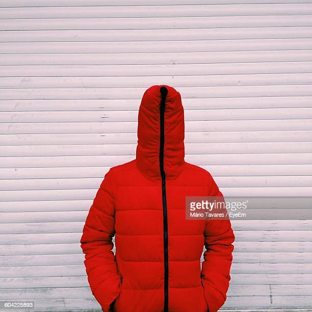 Person Standing In Wearing Red Hood Against Wall