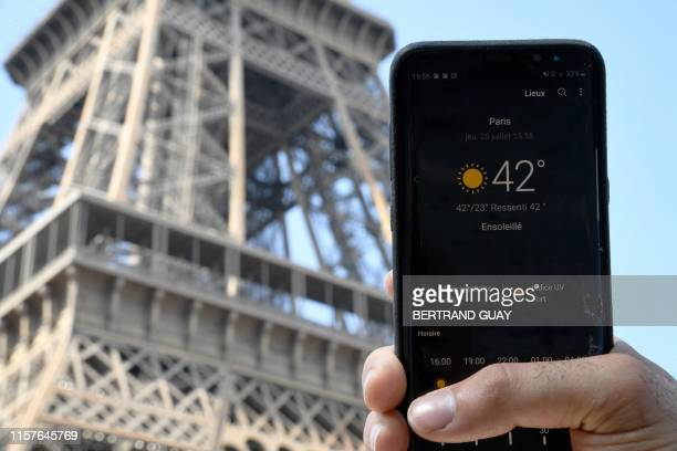 A person standing next to the Eiffel Tower holds a smartphone indicating a temperature of 42 degrees Celsius on July 25 2019 in Paris as a new...