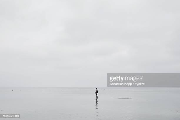 Person Standing On Beach Against Sky