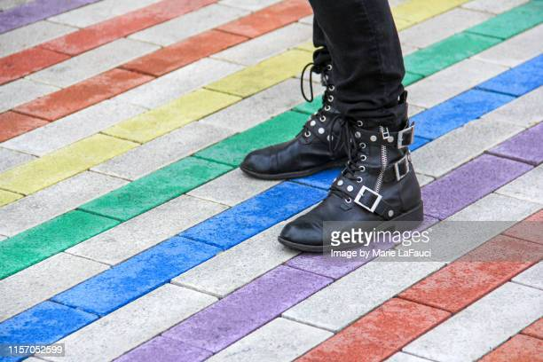 person standing on colorful rainbow sidewalk - leather boot stock pictures, royalty-free photos & images