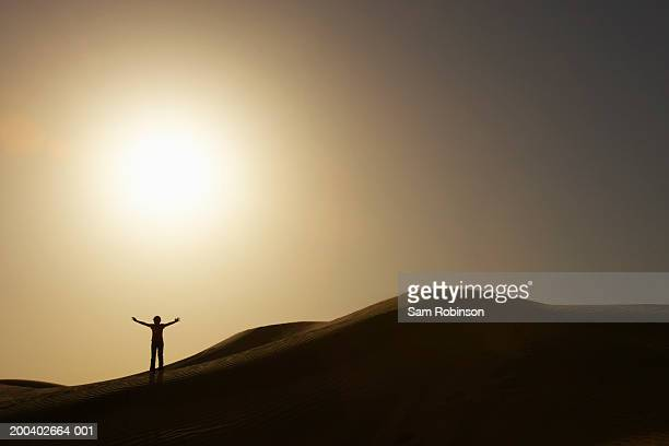 Person standing on desert dune, arms outstretched