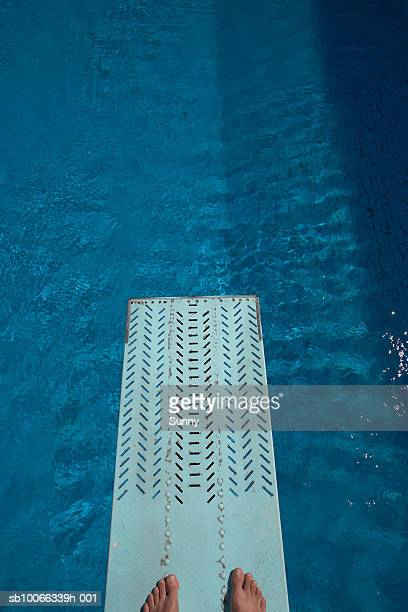 Person standing on diving board over swimming pool, low section