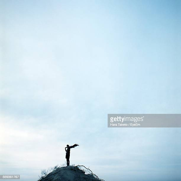 Person Standing On Hill Against Sky