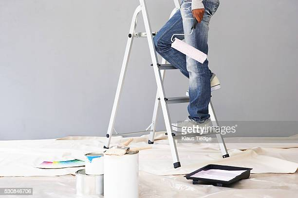 Person standing on ladder holding paint roller